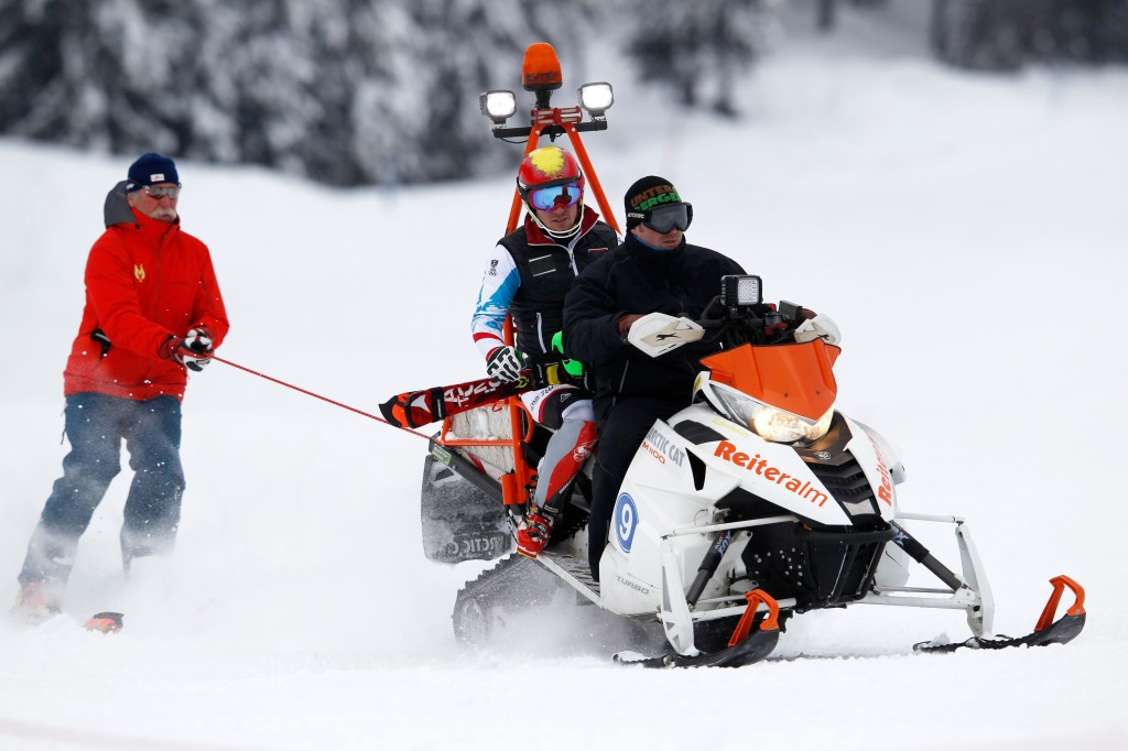 Marcel Hirscher's father, Ferdinand, hitches a ride off the back of a snow machine during training in Reiteralm. GEPA