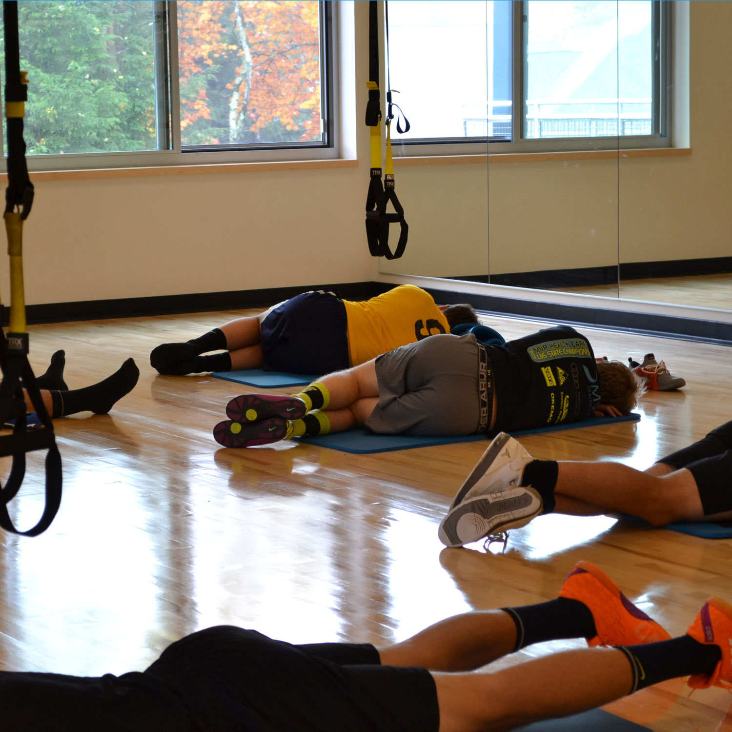 Athletes stretch out in the yoga studio space outfitted with TRX equipment.